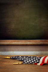 School blackboard with American flag on desk