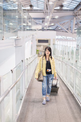 Asian woman traveler dragging  carry on luggage suitcase corridor walking to departure gates at airport terminal