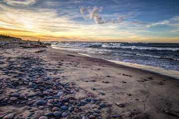 Scenic Windy Beach Sunset Background. Wide sandy beach with waves crashing on the shore at Whitefish Point on the coast of Lake Superior. Wide angle with rocks in foreground and waves at the horizon.
