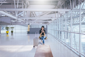 Beautiful Asian woman traveler using mobile phone in airport, Lifestyle using cell phone connection concept,while waiting for her flight