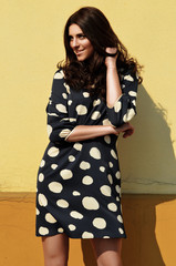 Smiling young woman in polka dot dress