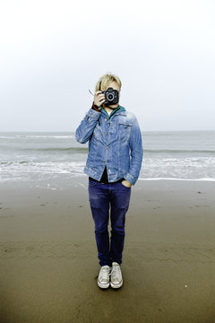 Young man standing on the beach making a photo at the camera
