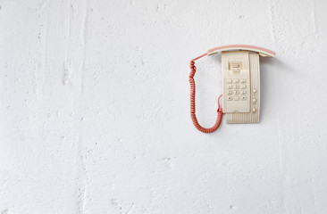 Dead telephone hanging on white wall