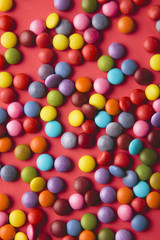 Close up of a pile of colorful chocolate coated candy on red background.