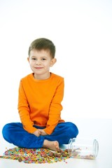 Kid sitting cross-legged with sweet jar spilled