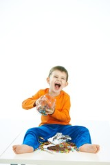 Mischievous boy with sweets jar sitting on floor