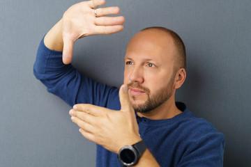mann plant etwas und schaut durch einen fingerrahmen