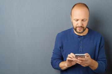 mann schaut auf sein handy und schreibt eine nachricht