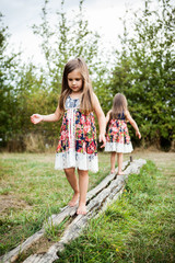 Twin sisters walking on a log