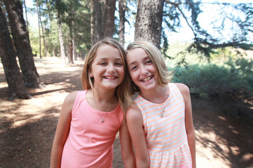 Portrait of happy twin sisters in a forest