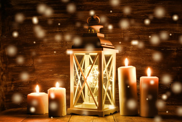 Vintage Lantern with burning candles and pine cones on wooden table. Snow overlay.