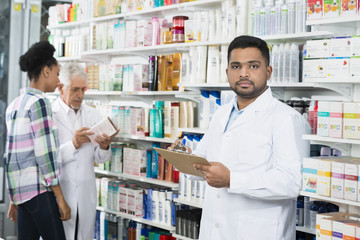 Chemist Holding Clipboard While Colleague And Customer Standing