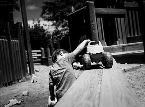 child plays with construction truck toys