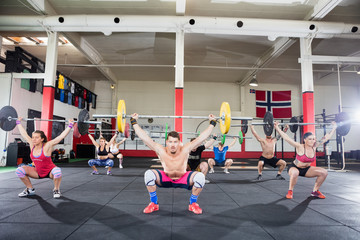 Trainer With Clients Crouching While Lifting Barbells