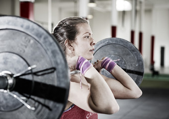 Confident Young Woman Lifting Barbell