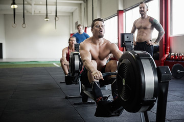 Man Exercising On Rowing Machine While Instructor Looking At Him