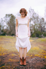Woman with Red Hair Wearing Vintage White Dress in Country