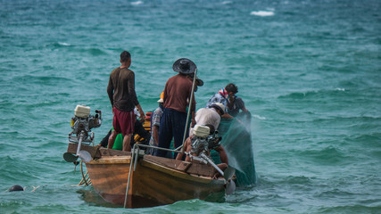 The fishermen on the fishing boat working together to harvest the fish from the sea with the fishing net