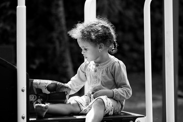 Portrait of young child coloring intently at a park