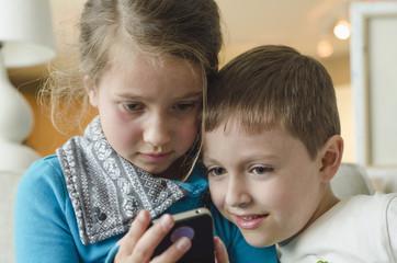 Kids together using smartphone indoors
