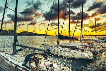 Sailing yachts moored at the pier at sunset