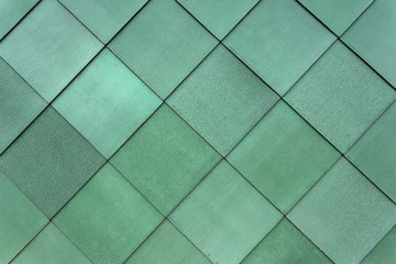 Square green cladding fastened to the exterior of a building to form a pattern