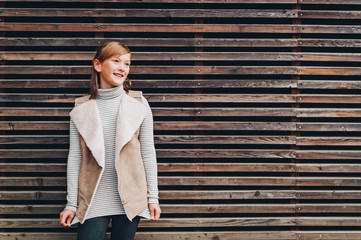 Outdoor fashion portrait of pretty little preteen girl of 10 years old, wearing beige vest, posing against brown wooden background
