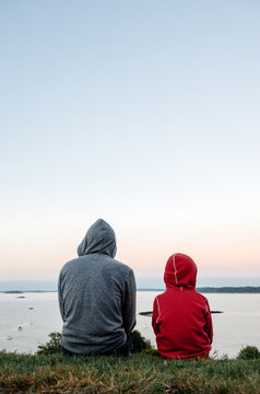 Father and son sit together on a hill, looking at the ocean