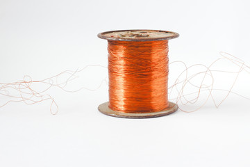 Copper wire spool. Red insulated wire wound up on plastic spindle. End of wire is stripped showing bare copper. Isolated on a white background. Room for text, copy space. Horizontal photo. .