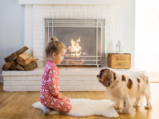 little girl in holiday pajamas sits in front of the fire with her dog
