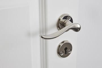 Metallic classic door knob on a white door. Closed