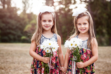 Portrait of twin sisters holding flowers in a park