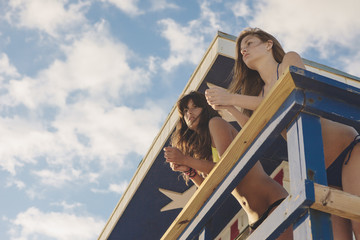 Young Women Friends in Bikini Swimsuit Hanging Out in Lifeguard Hut in South Beach Miami