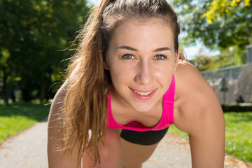 Cute young woman sporty girl with pink top ,workout outdoor
