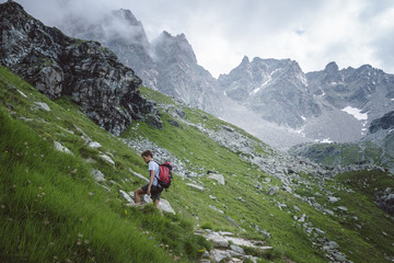 Man with backpack walking in mountain.