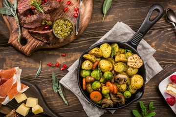 In de dag Klaar gerecht Fried potatoes with vegetables and herbs on wooden background. Healthy food concept. Overhead shot.