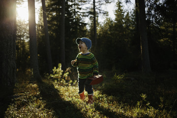 Cute little boy with red boots standing in the forest.
