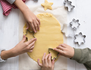 Children cut out of dough Christmas cookies. Preparing for Christmas. New year's concept. Top view flat layout