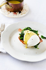 Eggs benedict florentine with hollandaise sauce, spinach and bacon