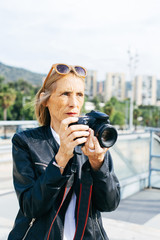 Mature woman taking photos with her camera in the city.