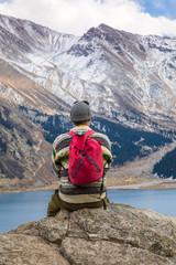 a man sits on a mountain, a mountain lake.Big Almaty Lake, Kazakhstan, Almaty