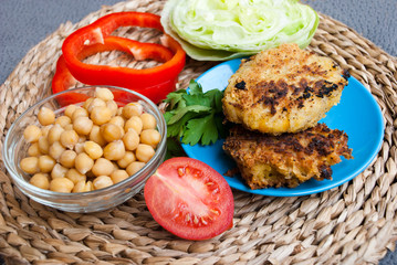 Falafel with tomato, bowl of chickpea and cilantro on gray background. Healthy food, vegetarian cutlets.