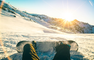 Foto auf Acrylglas Wintersport Snowboarder sitting at sunset on relax moment in french alps ski resort - Winter sport concept with adventure guy on top of mountain ready to ride down - Legs view point with teal and orange filter