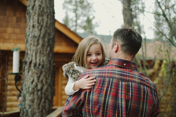 father carrying excited daughter into cabin