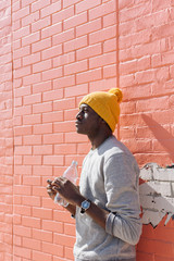Portrait of a black man leaning against a brick wall