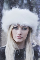Portrait of a beautiful young girl in snow