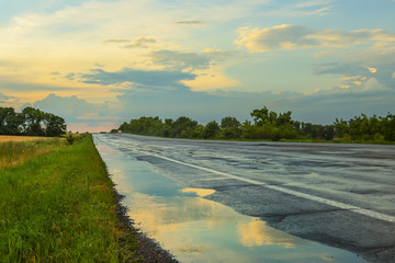 Fotobehang - The road is asphalt after the rain at sunset. Reflection of clouds and sky in a puddle on the roadside. A calm evening look.