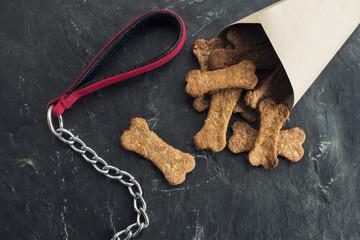 Bodegón de galletas con forma de hueso junto a una cadena de perro