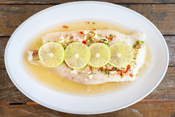 Steamed fish in lime on wooden table brown with thai style