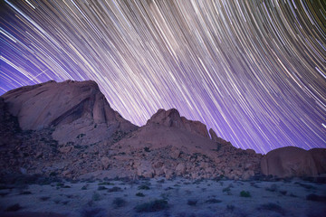 Timelapse of stars in night sky over mountains